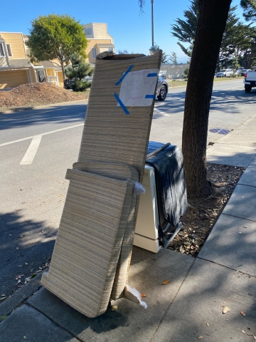 Photo of couch and appliance on the sidewalk waiting for pickup